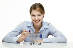 Young woman with shopping cart. Young woman with a miniature shopping cart Stock Image