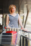 Young woman with shopping cart Royalty Free Stock Photos