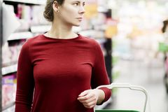 Young woman with shopping cart in supermarket. The girl in the background of the store looks at the goods. Shopping concept royalty free stock photo
