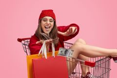 Young woman in shopping cart throwing money. Excited young female in bright trendy outfit holding paper bags and spending money while riding shopping trolley stock photos