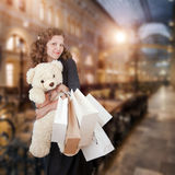 Young woman in shopping center. Portrait of young woman with teddy bear and paper bags in shopping center Royalty Free Stock Photo
