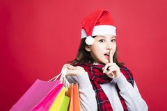 Woman shopping for christmas gifts with secret gesture Royalty Free Stock Photos