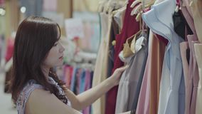 Woman shopping in a clothing store. Young woman shopping in a clothing store stock footage