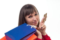 Young woman shopping with credit card holding colourful paper ba Royalty Free Stock Photography