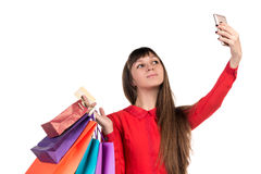 Young woman shopping with credit card holding packages doing sel. Young woman shopping with credit card holding colourful paper bags and packages does selfie Royalty Free Stock Photo