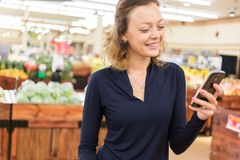 Grocery shopping. Young woman shopping in the fresh produce section at the grocery store Stock Photography