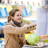 Young woman shopping for fruits and vegetables. Beautiful young woman shopping for fruits and vegetables in produce departmant of a grocery store/supermarket ( Royalty Free Stock Images