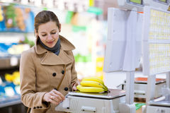 Young woman shopping for fruits and vegetables. Beautiful young woman shopping for fruits and vegetables in produce departmant of a grocery store/supermarket ( Royalty Free Stock Photos