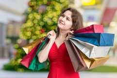 Young woman is shopping gifts for Christmas in shop and carrying many bags Royalty Free Stock Photos