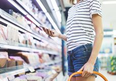 Young woman shopping healthy food in supermarket blur background. Close up view girl buy products using smartphone in store. Hipster at grocery using royalty free stock photos