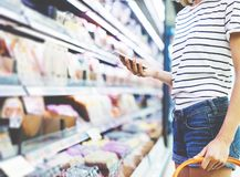 Young woman shopping healthy food in supermarket blur background. Close up view girl buy products using smartphone in store. Hipster at grocery using stock photo