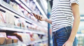 Young woman shopping healthy food in supermarket blur background. Close up view girl buy products using smartphone in store. Hipster at grocery using royalty free stock photography