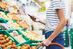 Young woman shopping healthy food in supermarket blur background. Female hands buy nature products using smart phone in store. Hipster at grocery using mobile royalty free stock image