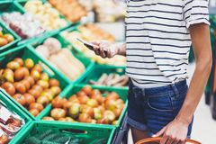 Young woman shopping healthy food in supermarket blur background. Female hands buy products tomato using smartphone in store. Hipster at grocery using stock photos