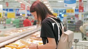 Young woman shopping healthy food in supermarket. Sale, shopping, consumerism and people concept. stock video footage