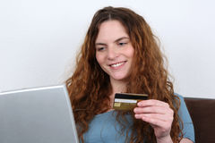 Young woman shopping on the internet with credit card Stock Image