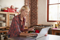 Young woman shopping on-line in her kitchen, waist up Royalty Free Stock Image