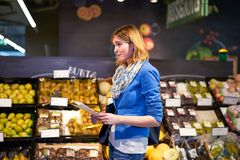 Young woman with shopping list in shop. Young woman staying confused with shopping list in grocery store Royalty Free Stock Photo