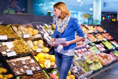 Young woman with shopping list. Young stylish woman in blue jacket staying confused with shopping list in grocery store Stock Photography