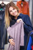 Young woman shopping and looking at some clothing in a store. Royalty Free Stock Photo