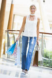 Young woman shopping in mall. Carrying bags Stock Photo