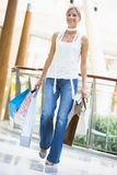 Young woman shopping in mall. Carrying bags Royalty Free Stock Images