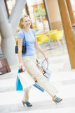 Young woman shopping in mall. Carrying bags Royalty Free Stock Photos