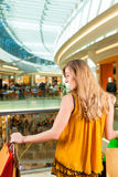 Young woman shopping in mall with bags. Young happy woman with shopping bags having fun while shopping in a mall stock photo