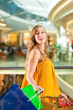 Young woman shopping in mall with bags. Young happy woman with shopping bags having fun while shopping in a mall royalty free stock image