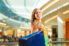 Young woman shopping in mall with bags. Young happy woman with shopping bags having fun while shopping in a mall royalty free stock photos