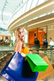 Young woman shopping in mall with bags. Young happy woman with shopping bags having fun while shopping in a mall royalty free stock photography