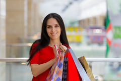 Young Woman Shopping in Mall Holding Paper Bags. Young Woman Shopping in Mall - Red dress, shopping and gift bags Stock Image