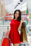 Young Woman Shopping in Mall with Shopping Bags. Young Woman Shopping in Mall - Red dress, shopping and gift bags Stock Images