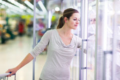 Young woman shopping for meat in a grocery store Royalty Free Stock Image