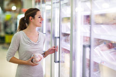 Young woman shopping for meat in a grocery store Stock Images