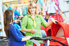 Young woman shopping during pregnancy. Pregnancy shopping. Female saleswoman selling perambulator for baby carriage to young pregnant women at shop store Royalty Free Stock Photos