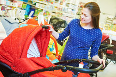 Young woman shopping during pregnancy. Pregnancy shopping. Pregnant woman choosing pram for newborn carriage at baby shop store Stock Images