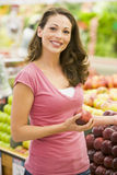 Young woman shopping in produce department. Of supermarket Stock Photography