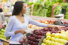 Young woman shopping in produce section. Of supermarket Royalty Free Stock Photography