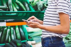 Young woman shopping purchase healthy food in supermarket blur background. Close up view girl buy products using smartphone in sto. Re. Hipster at grocery using stock image