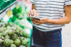 Young woman shopping purchase healthy food in supermarket blur background. Close up view girl buy products using smartphone in sto stock photography
