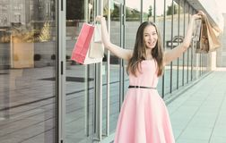 Young woman after shopping with purchases standing at the glass building. She raised her hands up with paper bags. Smiles and looks at the camera Stock Images