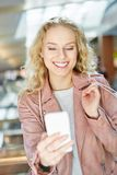 Young woman while shopping reads a text message. On the smartphone and is happy Stock Photo