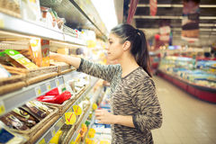 Young woman shopping for recipe ingredients in a large supermarket.Shopping for groceries,household,health and beauty.Self service. Choosing from variety of Royalty Free Stock Photography