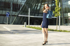 Young woman after shopping standing on the street. Royalty Free Stock Photos