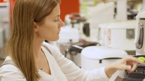 Young woman shopping in store buying kitchen appliances. Picking up deep fryer grille. White goods on background stock footage