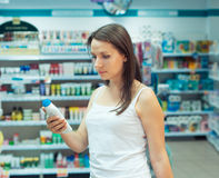 Young woman shopping in the store household chemicals and cosmetics. Beautiful young woman shopping in the store household chemicals and cosmetics royalty free stock images