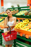 Young woman shopping in a supermarket in the department of fruit Stock Images