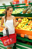 Young woman shopping in a supermarket in the department of fruit Stock Photos