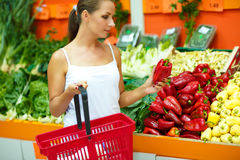 Young woman shopping in a supermarket in the department of fruit Royalty Free Stock Photos